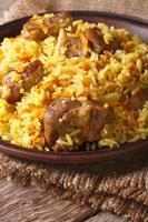 Pilaw mit Fleisch und Gemüse Nahaufnahme auf einem Teller. Vertikale