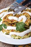 Zucchini-Pfannkuchen mit Sauerrahm-Nahaufnahme auf dem Tisch foto
