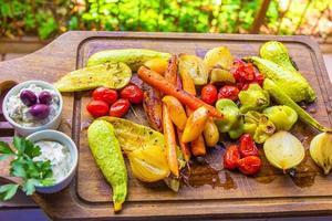 schöner Salat aus geröstetem Gemüse mit Olivensauce auf Brüstung. foto