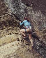 Frau klettert auf den Felsen foto