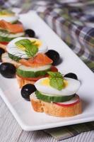 Canape mit gekochtem Ei, Gurke, Radieschen, Lachs vertikal foto