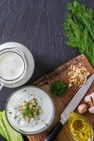 Zutaten für die Taratorsuppe - Gurke, Dill, Walnüsse, Knoblauch, Joghurt, Öl foto