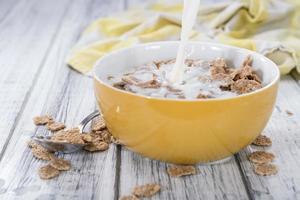 Gießen Sie Milch auf eine Portion Cornflakes foto