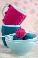 helle Wollknäuel in blauen Tellern und handgemachtem Herzen foto