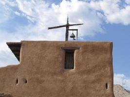 Adobe Haus mit Glocke und Kreuz foto
