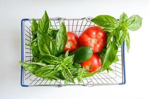 frisches Gemüse im Einkaufswagen lokalisiert auf weißem Hintergrund foto