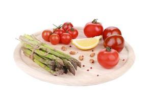 Spargel und Tomaten auf Holzbrett.