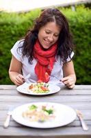 Frau, die eine Mahlzeit im Freien genießt foto