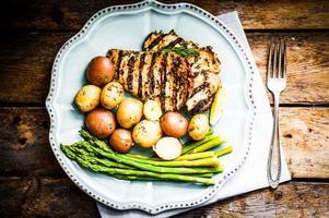 gegrilltes Huhn mit Kartoffeln und Spargel auf hölzernem Hintergrund foto