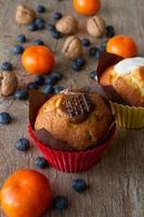 Schokoladen-Vanille-Zitronen-Muffins mit Mandarinen und Walnüssen foto