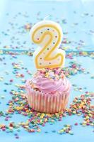 kleiner Cupcake mit rosa Zuckerguss und Streuseln foto