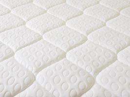 weiße Federkernmatratze mit ovalen Mustern