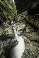 versteckte Schlucht mit schnell fließendem Wasser und einem künstlichen Weg foto