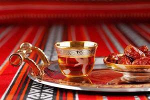 ikonischer abrian Stoff mit arabischem Tee und Datteln foto