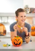 Frau, die Süßes oder Saures Süßigkeiten in der mit Halloween dekorierten Küche isst