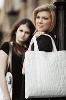 zwei junge Frauen, die auf einer Stadtstraße gehen foto
