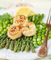 leckeres Abendessen mit gerösteten Jakobsmuscheln, Spargel und Erbsen foto