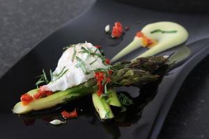 Chefkoch bereitet Spargel mit pochierten Quial-Eiern zu