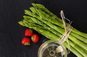 grüner Spargel mit Weißwein und Erdbeeren foto