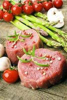 rohes Steak mit grünem Spargel auf Holzbrett foto