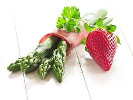 grüner spargel mit einer erdbeere