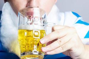 Mann mit bayerischer Flagge trinkt Glas Bier foto