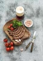 Grillwürste mit Gemüse auf rustikalem Servierbrett und Becher
