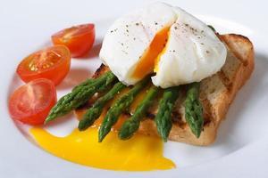 Toast mit Spargel, pochiertem Ei und Tomaten Nahaufnahme foto