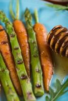 Gegrillte frische Karotten und Spargel mit Glasur auf Teller foto