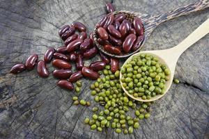 grüne Bohnen und rote Bohnen im Holzlöffel.