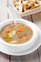 zuppa di legumi, fave e carote con gocce di olio
