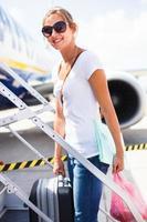 weiblicher Passagier beim Einsteigen in ein Flugzeug foto