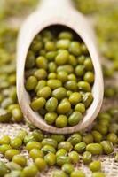 grüne Mungobohnen der gesunden Nahrung im Holzlöffel auf Weinlese foto