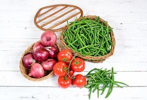 Korb mit grünen Bohnen mit Tomaten und Zwiebeln foto