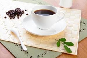 Bohne und heißer Kaffee mit grünem Blatt