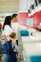 Einchecken der Familie am Schalter der Fluggesellschaft foto