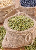grüne Bohnen oder Kichererbsen in Säcken kleiner Leinensack foto
