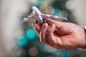 Nahaufnahme der Mannhand, die Modell des Flugzeugs hält foto