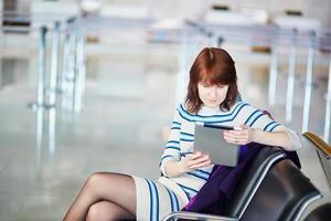 junger Passagier am Flughafen mit ihrem Tablet foto