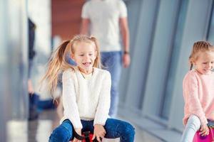 entzückendes kleines Mädchen am Flughafen, das auf Koffer sitzt foto