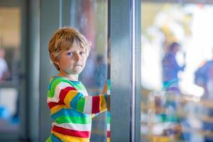 kleiner müder Junge am Flughafen, auf Reisen foto