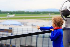 kleiner Junge, der Flugzeuge im Flughafen betrachtet foto