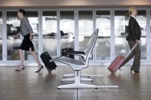Geschäftsfrau, die mit Gepäck im Flughafenterminal geht foto