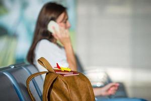junge Frau, die am Telefon spricht, während sie an Bord wartet foto