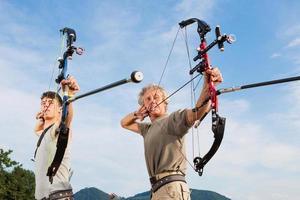 Bogenschützen ... Vater und Sohn üben das Schießen von Zielen