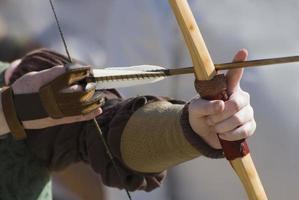 Nahaufnahmefoto der Hände eines Bogenschützen, die auf seinen Bogen zielen