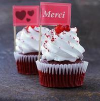festliche Cupcakes aus rotem Samt mit einer Geschenkkomplimentkarte foto