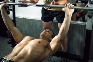 Mann beim Gewichtheben mit Personal Trainer foto
