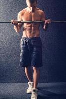 Bodybuilder beim Heben von Gewichten im Fitnessstudio foto
