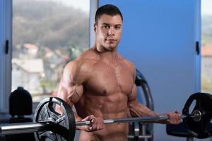 junger Mann, der Gewichte mit Langhantel hebt foto